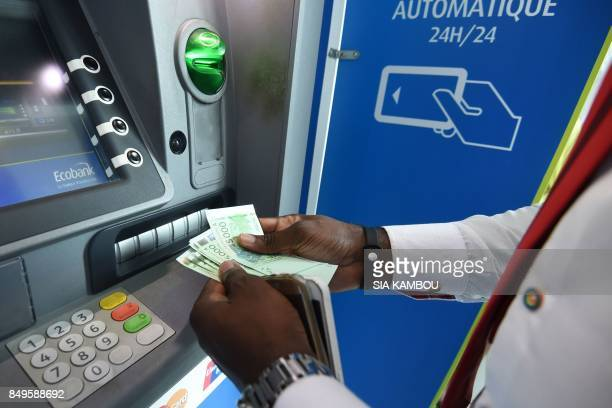 A man uses an Ecobank Ivory Coast cash dispenser on September 18 2017 in Abidjan EcobankIvory Coast the Ivorian subsidiary of panAfrican bank Ecobank...