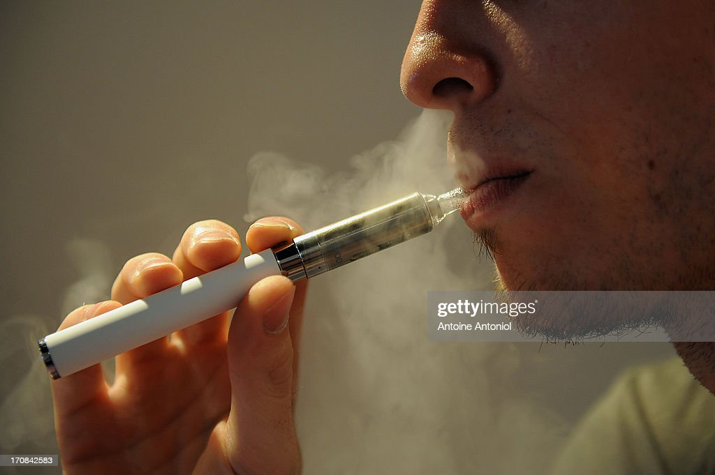 A man uses an electronic cigarette at a store on June 19, 2013 in Paris, France. French Social Affairs and Health Minister Marisol Touraine announced the government's intention to ban the electronic cigarette in public places and for smokers under 18 years.