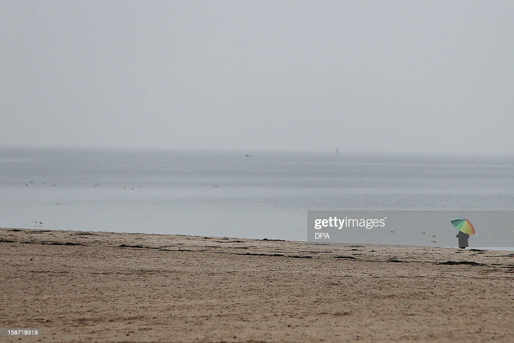 A man uses an umbrella as he strolls at the Baltic Sea beach of Travemuende, northern Germany on December 25, 2012.