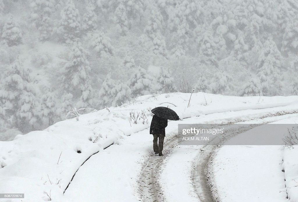 A man uses an umbrella as he walks under the snow in Ankara on February 6, 2016. / AFP / ADEM ALTAN