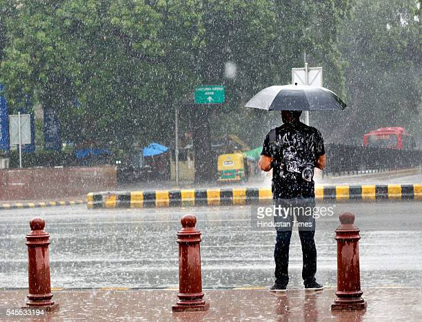 A man uses an umbrella to protect himself from Monsoon rains on July 8 2016 in New Delhi India Rains hit several parts of the national capital which...