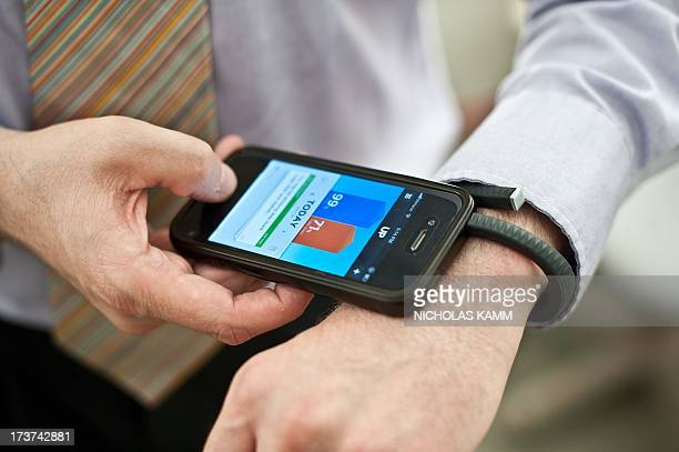A man uses an UP fitness wristband and its smartphone application in Washington on July 16 2013 Jawbone the San Franciscobased company behind 'smart'...