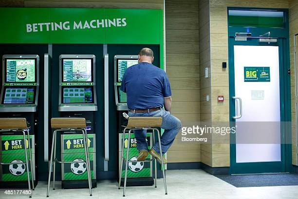 A man uses betting machines at a Paddy Power Plc bookmakers in London UK on Tuesday Aug 25 2015 Ireland's biggest bookmaker Paddy Power 'paid out...