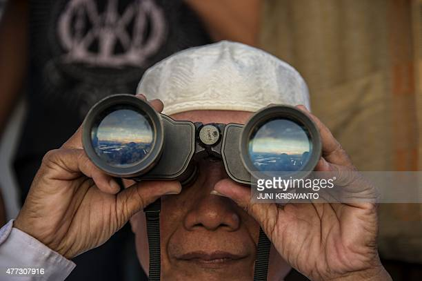 A man uses binoculars to spot the new moon to mark the beginning of Ramadan in Surabaya eastern Java province on June 16 2015 Indonesia the world's...