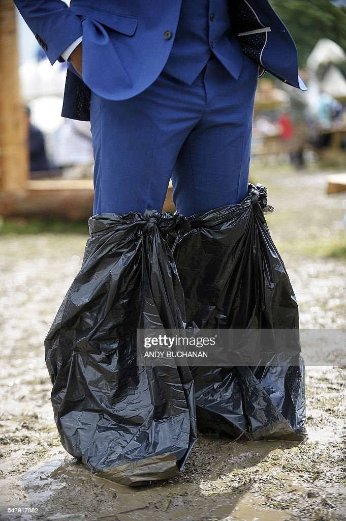 A man uses black bin bags to protect his footwear and suit trousers from the mud on day four of the Glastonbury Festival of Music and Performing Arts on Worthy Farm near the village of Pilton in Somerset, south west England on June 24, 2016. / AFP / Andy Buchanan