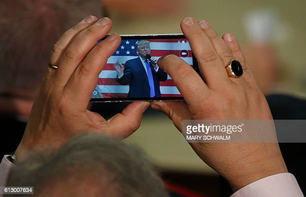 A man uses cell phone to take a photo of Republican presidential candidate Donald Trump as he speaks at a town hall event on October 6 2016 in...