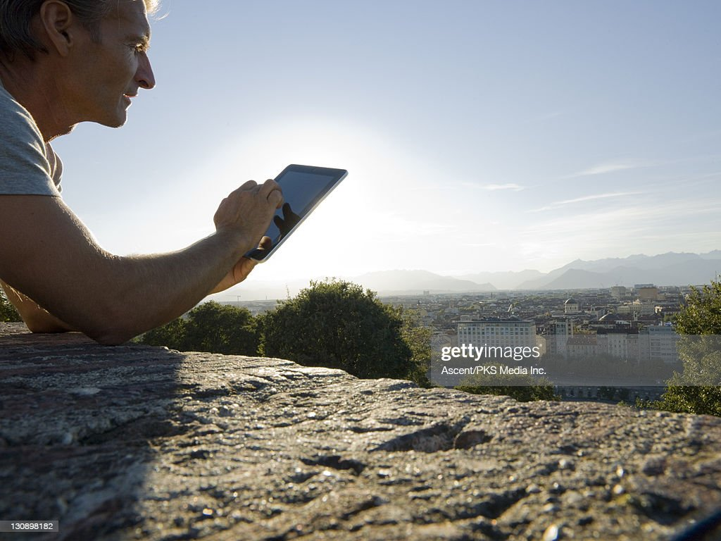 Man uses digital tablet above city, mountains : Stock Photo