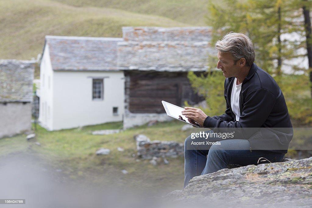 Man uses digital tablet in rural setting : Stock Photo