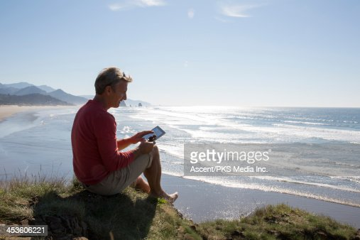 Man uses digital tablet on bluff above beach : Stock Photo