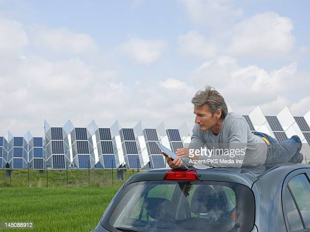 Man uses digital tablet on car roof,solar facility