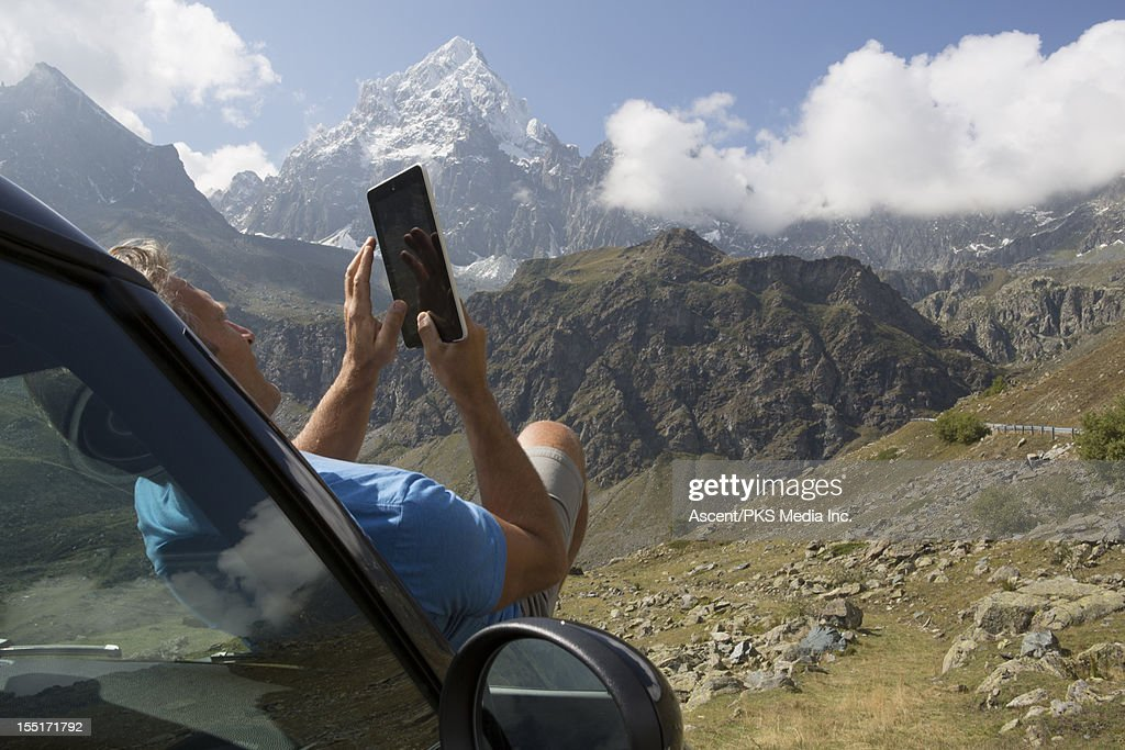 Man uses digital tablet on hood of car, in mtns : Stock Photo