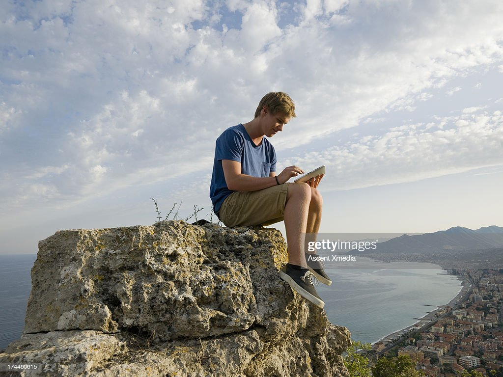 Man uses digital tablet, on rock above sea : Stock Photo
