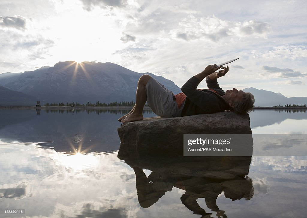 Man uses digital tablet on rock, mtn lake : Stock Photo