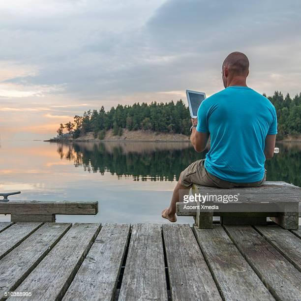Man uses digital tablet on seaside pier