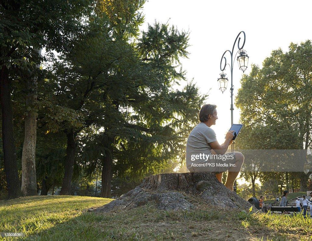 Man uses digital tablet on stump, in urban park : Stock Photo