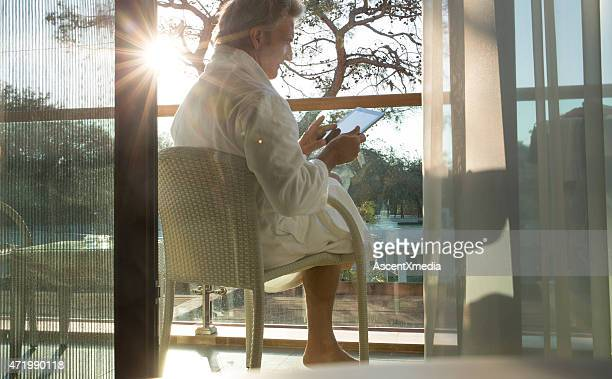 Man uses digital tablet on terrace, sunrise
