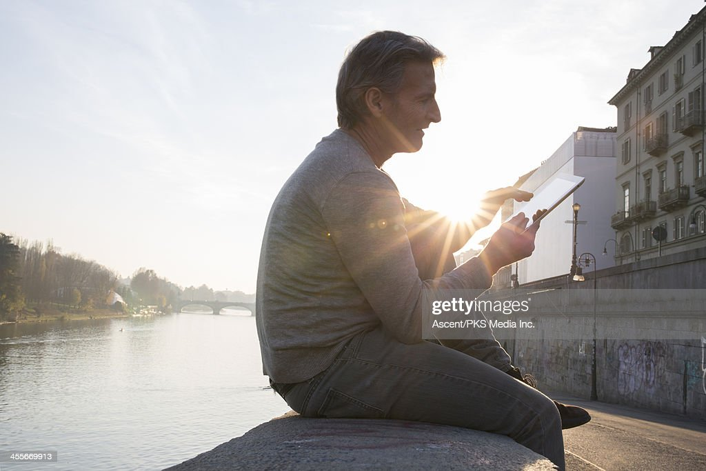 Man uses digital tablet on wall above river, city : Stock Photo