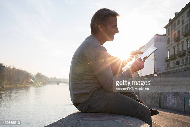 Man uses digital tablet on wall above river, city