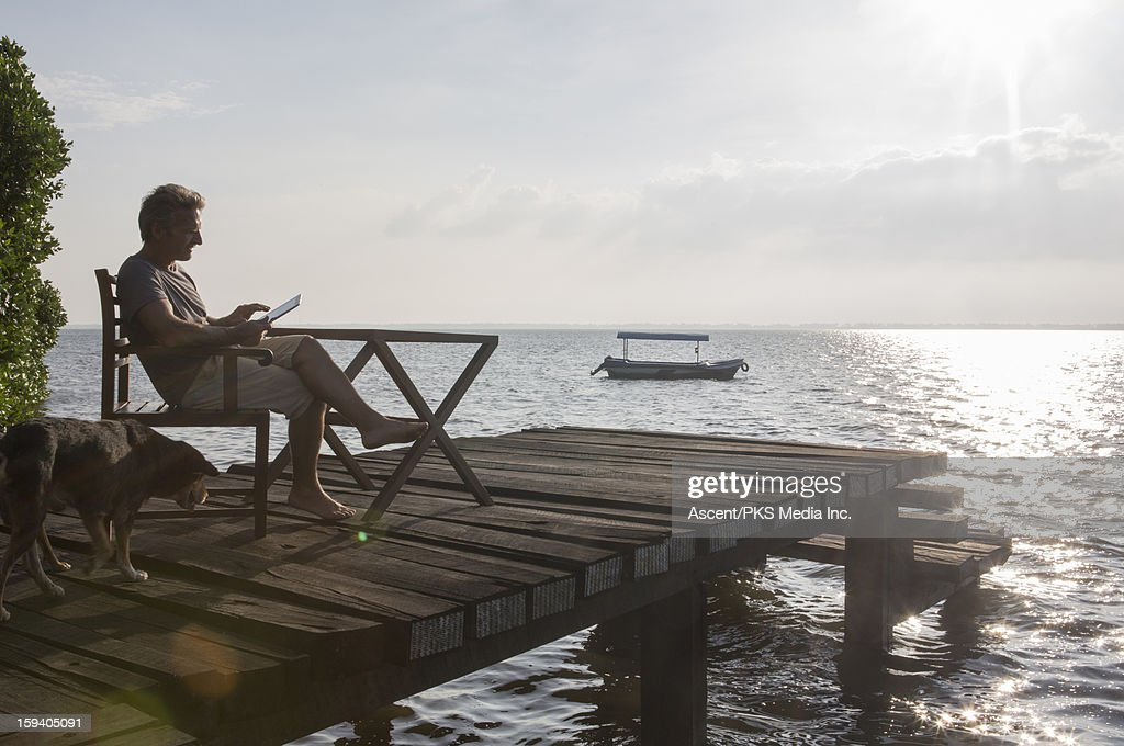 Man uses digital tablet on wharf,as dog approaches : Stock Photo