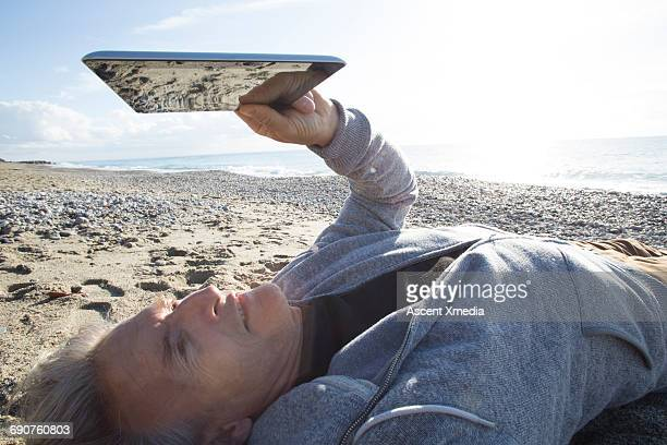 Man uses digital tablet while lying on beach