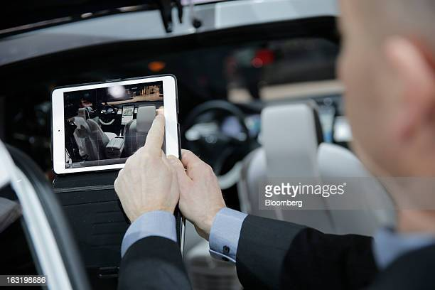 A man uses his Apple Inc iPad to take a photograph of the interior of a Tesla Model X electric prototype automobile produced by Tesla Motors Inc on...