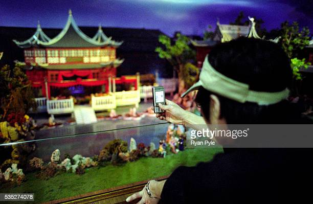 A man uses his camera phone to take a picture of a small temple at the Urban Planning Museum Shanghai is China's largest and most dynamic city It's...