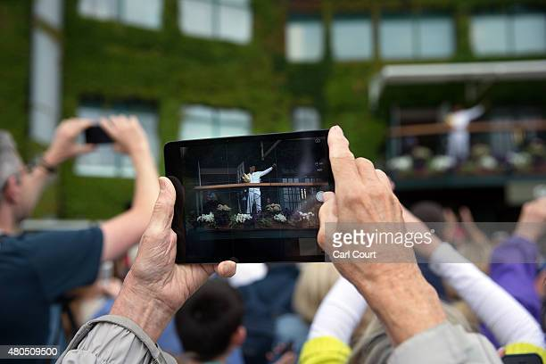 A man uses his iPad to film Novak Djokovic of Serbia as he celebrates with his winner's trophy on the clubhouse balcony in front of fans after...