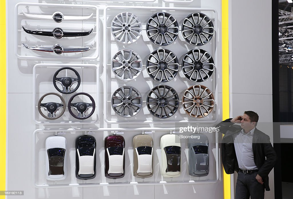 A man uses his mobile phone as he stands alongside accessories for Opel automobiles on the first day of the 83rd Geneva International Motor Show in Geneva, Switzerland, on Tuesday, March 5, 2013. This year's show opens to the public on Mar. 7, and is set to feature more than 100 product premiers from the world's automobile manufacturers. Photographer: Valentin Flauraud/Bloomberg via Getty Images