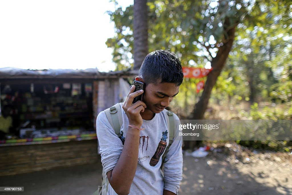 A man uses his mobile phone at a store on Dahanu Road in Kainad, Maharashtra, India, on Saturday, Dec. 21, 2013. The construction of 600,000 kilometers (373,000 miles) of country roads, addition of 327 million rural phone connections and a rise in literacy to record levels since Prime Minister Manmohan Singh took office in 2004 has helped double the growth rate of Indias food output. Photographer: Dhiraj Singh/Bloomberg via Getty Images