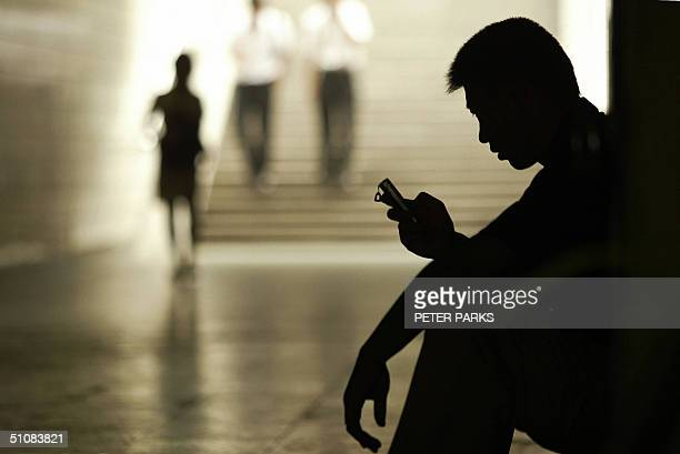 A man uses his mobile phone for messaging in an underpass in Beijing 20 July 2004 China has 300 million costconscious cellphone users many of whom...