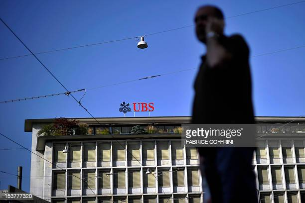 A man uses his mobile phone in front of the building of the Swiss banking giant UBS on August 23 2011 in the centre of Zurich UBS announced plans to...
