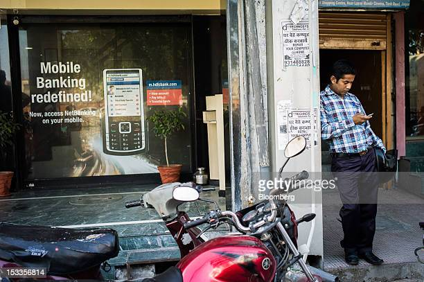 A man uses his mobile phone outside a Housing Development Finance Corp bank branch in Jaipur Rajasthan India on Wednesday Oct 3 2012 The Indian...