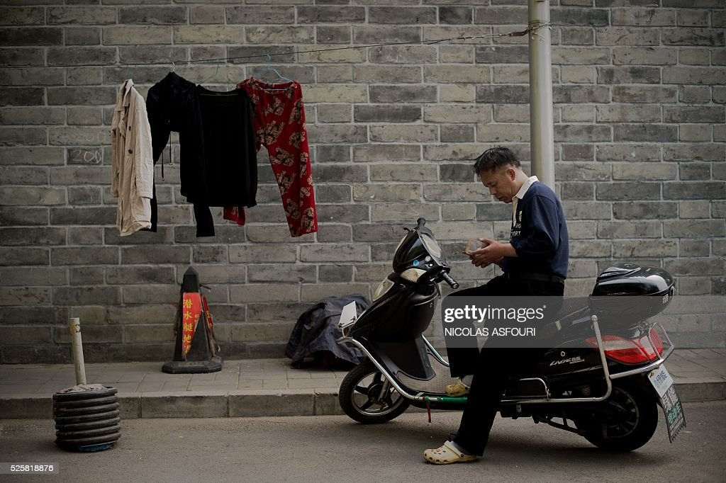 A man uses his phone as he sits on his electric bike on a street in Beijing on April 29, 2016. / AFP / NICOLAS