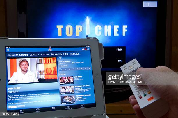 A man uses his remote control and his computer during the broadcast of a French channel TV program on March 15 2013 in Paris The recent increase of...