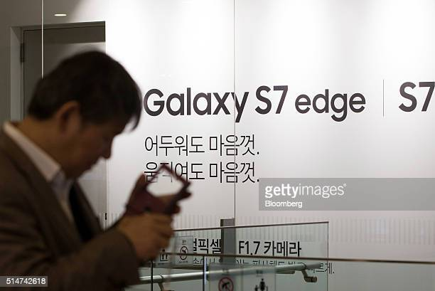 A man uses his smartphone in front of an advertisement for the Samsung Electronics Co Galaxy S7 and S7 Edge smartphone at the company's dlight...