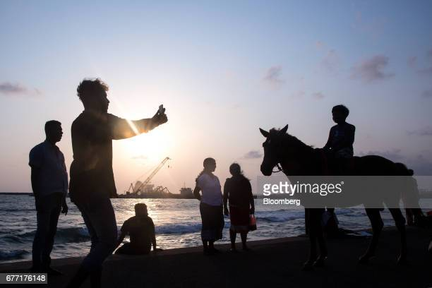 A man uses his smartphone to take a photograph of a child sitting on a horse at the sea front of Galle Face Green as the construction site of the...