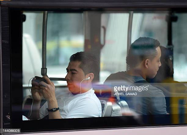 A man uses his smartphone while riding in a bus in Washington DC on May 9 2012 Mere weeks from a multibilliondollar debut on the stock market...