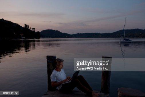 Man uses laptop computer on lake wharf, at dusk : Stock Photo