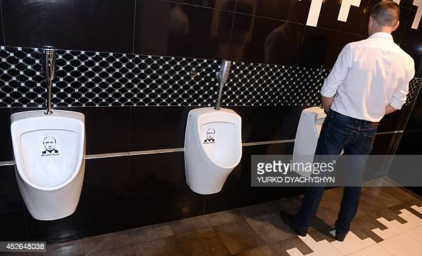A man uses one of the urinal decorated with a picture of Russian President Vladimir Putin and insulting words in the toilet of a popular restaurant...