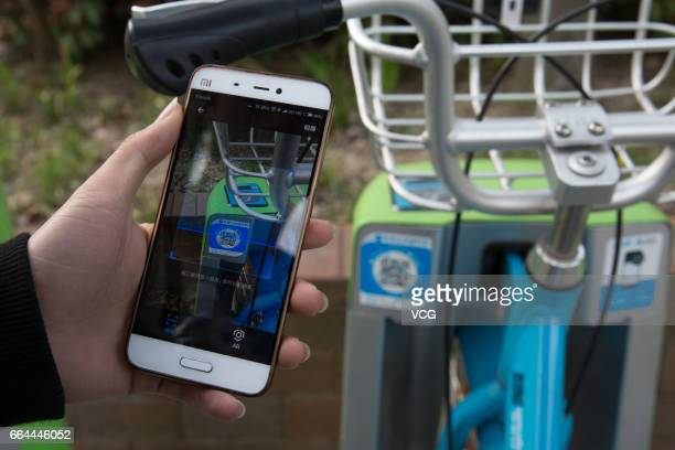 A man uses the Ant Financial Services Group's Alipay app to scan the QR code on a bicycle of the bikesharing scheme Changzhou Youon Public Bicycle...