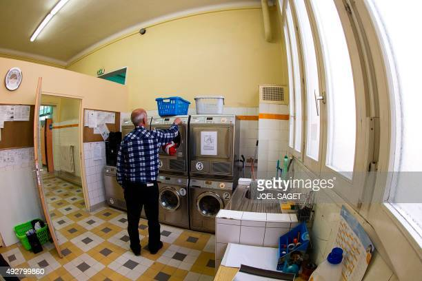 A man uses the laundry facilities of the association '11000 Potes' at a public bath in Paris on October 11 where homeless individuals can also store...
