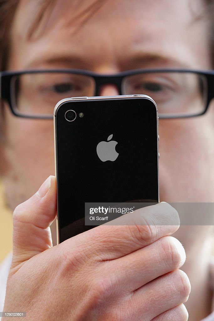 A man uses the new iPhone 4S after being one of the first customers in the Apple store in Covent Garden on October 14, 2011 in London, England. The widely anticipated new mobile phone from Apple has seen customers queue in cities around the world for hours to be amongst the first to buy the device.
