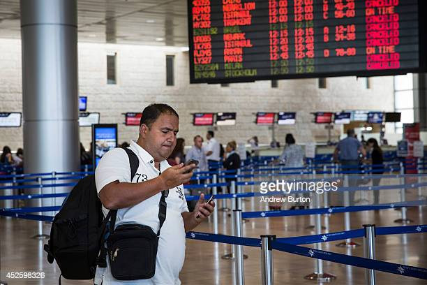 A man uses the phone while waiting at the departures gate of terminal three of Ben Gurion Airport on July 24 2014 in Tel Aviv Israel The Federal...