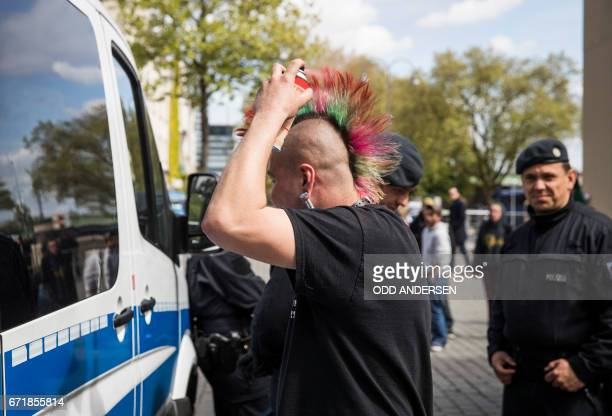 A man uses the window of a police car as a mirror to spray his hair in Cologne western Germany on April 23 2017 / AFP PHOTO / Odd ANDERSEN