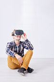 Young man behaves like a child while using virtual reality glasses