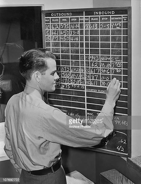 A man using a blackboard to chalk up the details of incoming and outgoing flights at an airport circa 1945