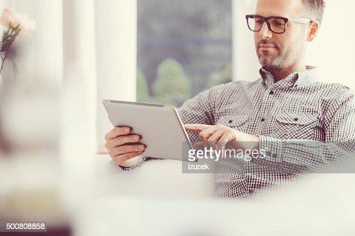 男性、デジタルタブレットを使用して自宅で