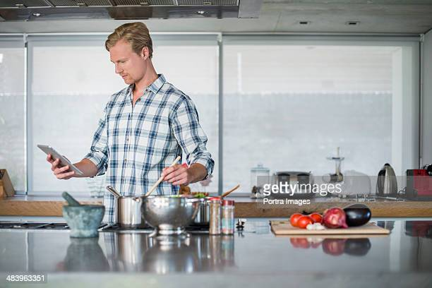 Man using a digital tablet in kitchen