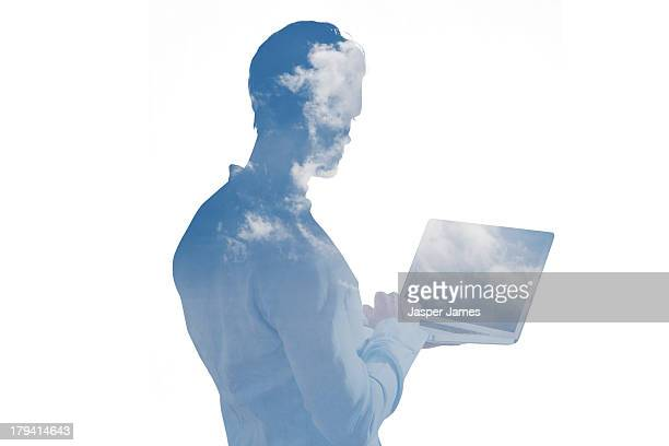 man using a laptop and blue sky with clouds