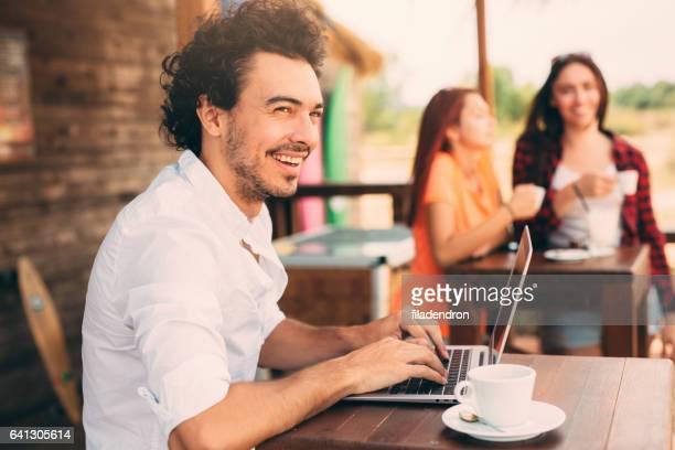 Man met een laptop in een strandbar